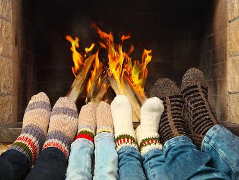 Семья в носках греется у камина на сайте nesu-teplo.ru